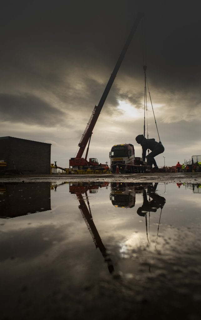 Messenger sculpture lifted onto lorry by crane against moody sky