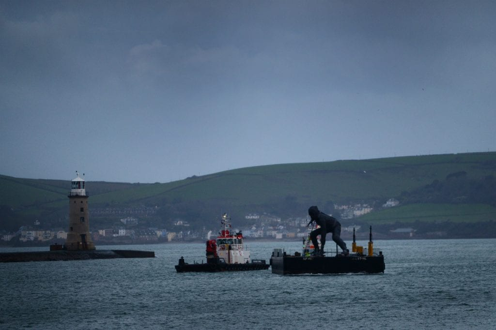 bronze Messenger sculpture on barge coming into Plymouth Sound
