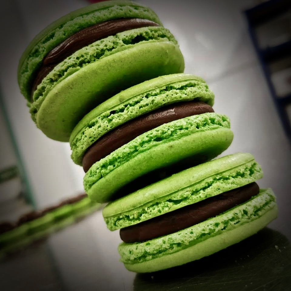 Tower of green macarons with chocolate filling.