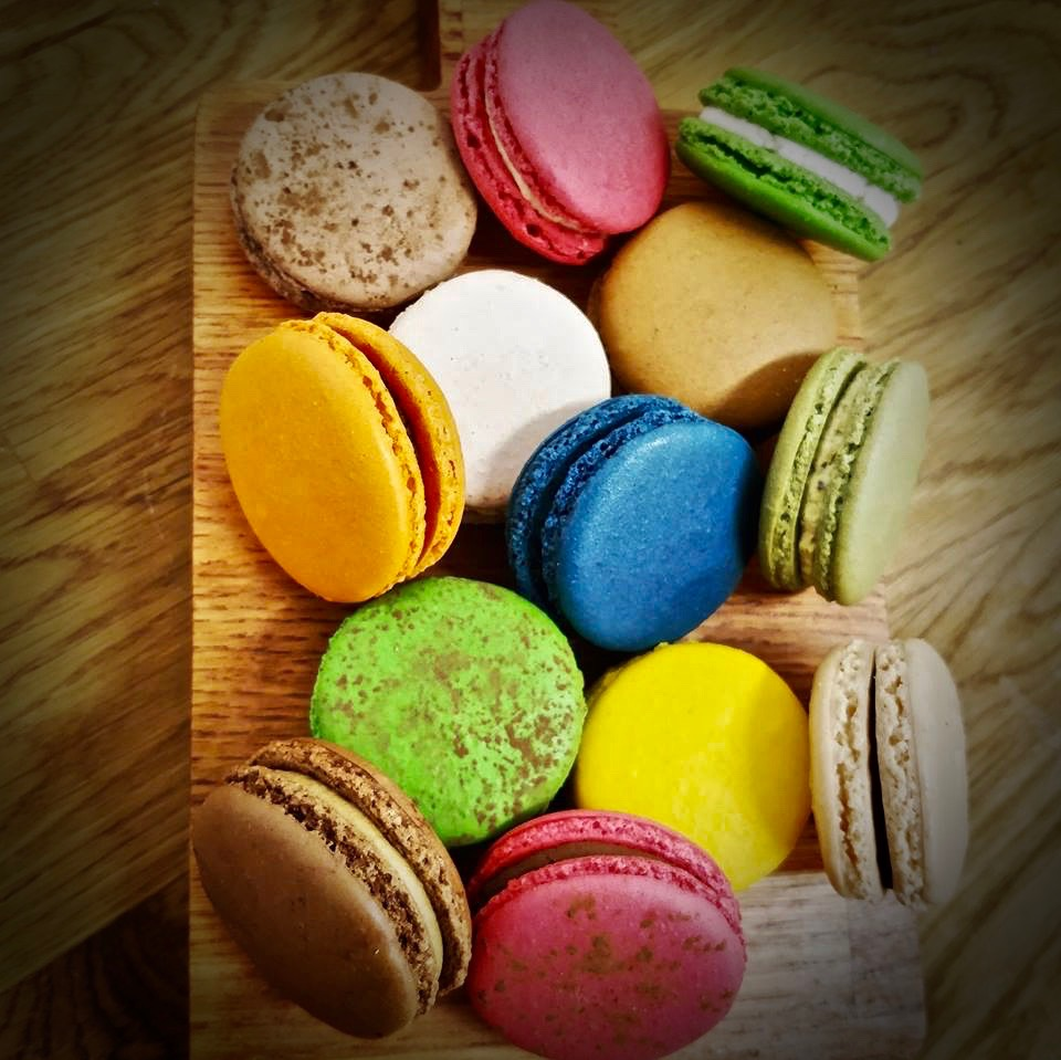 Several colourful macarons on a wooden surface.
