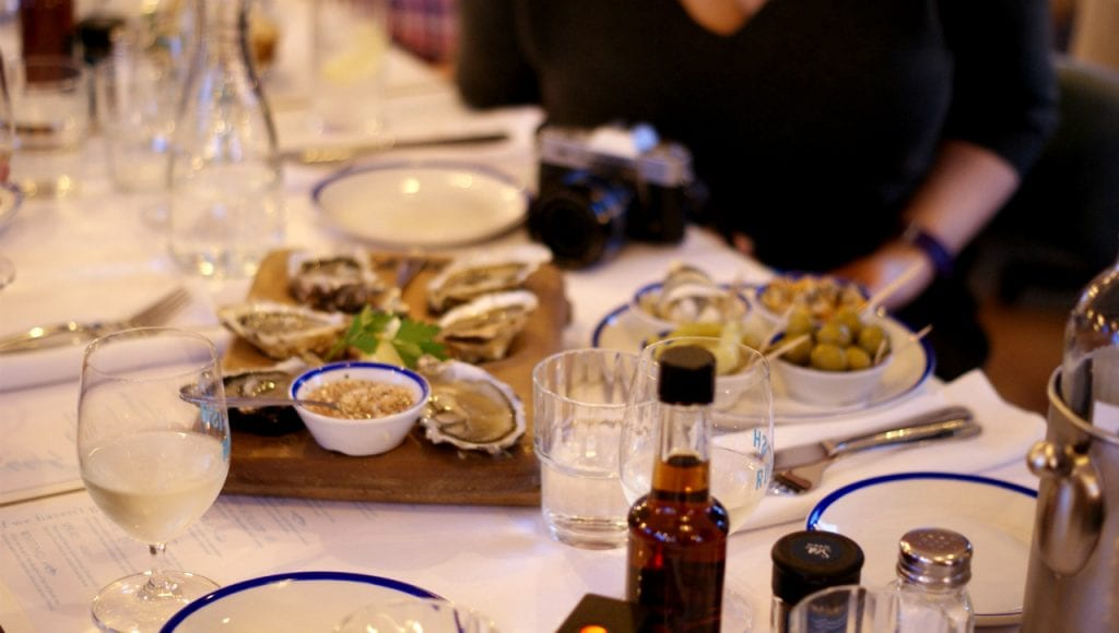 A board of oysters next to tapas dishes of olives, boquerones and guindilla peppers