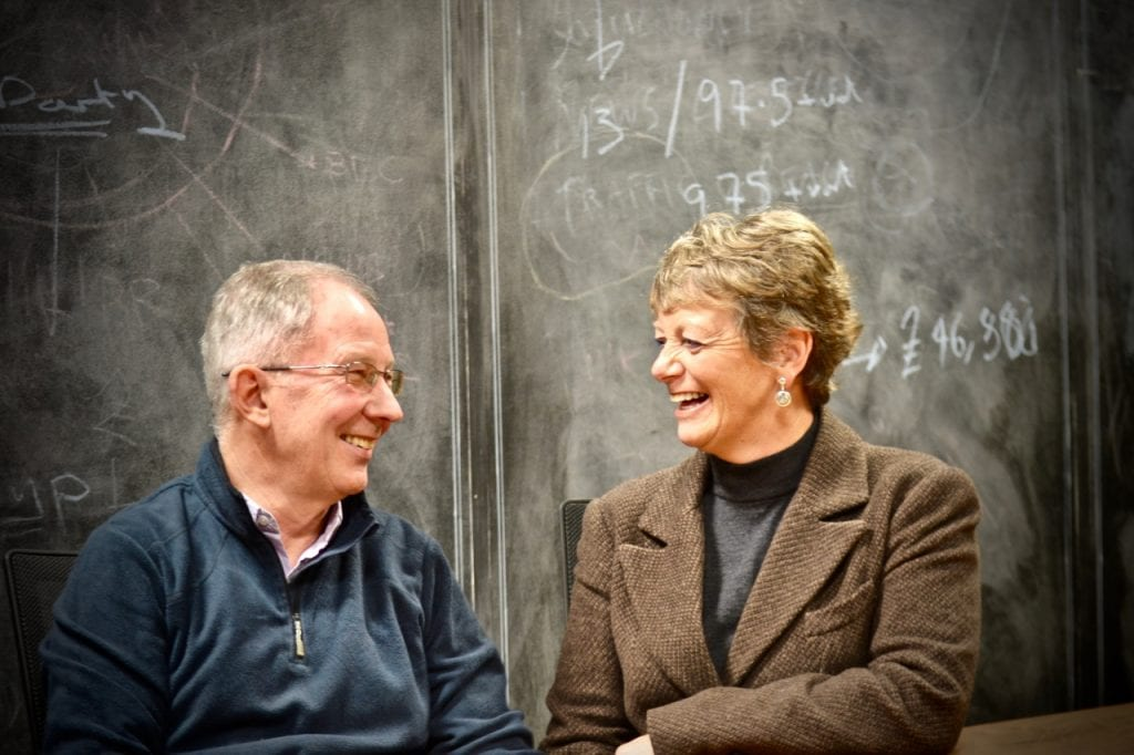 Tony and Stephanie Colston, founders of Retireista movement, laughing in front of blackboard