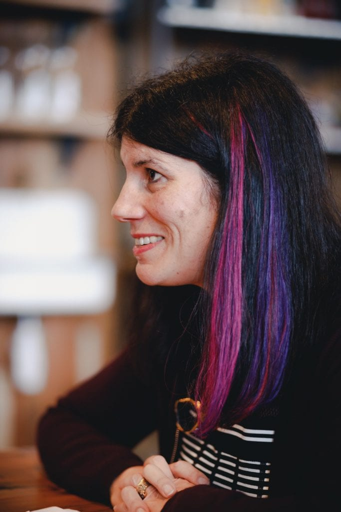 Side profile of Lucy Findlay with pink and purple stripes in her hair.