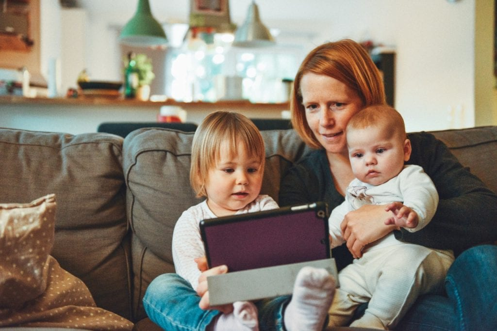 Mum with baby and toddler using a tablet.