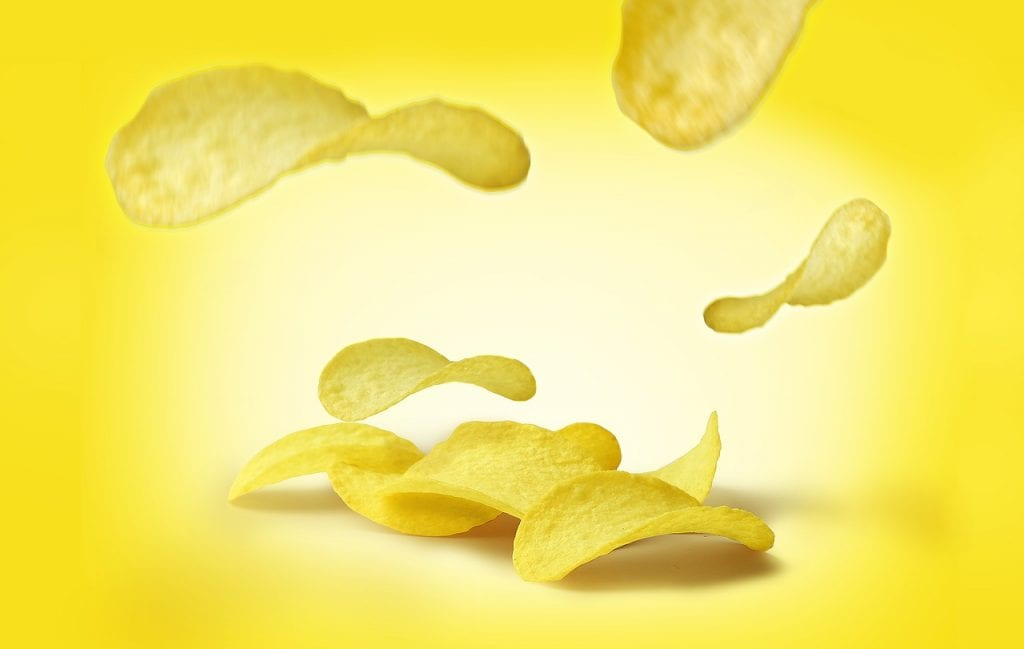 junk foods crisps on yellow background