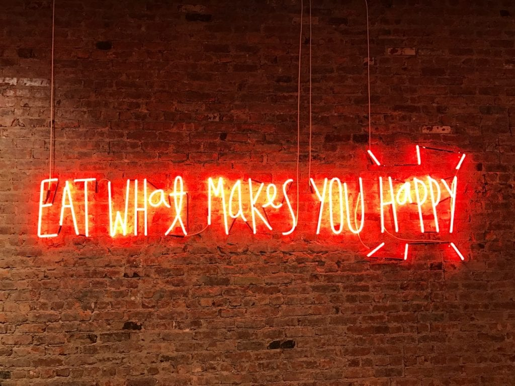 Red and yellow neon sign saying Eat What Makes You Happy against brick wall
