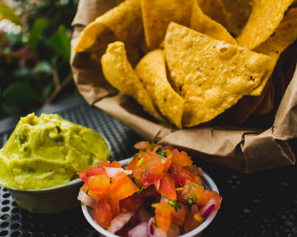 paper bag of tortilla chips next to bowls of tomato salsa and guacamole