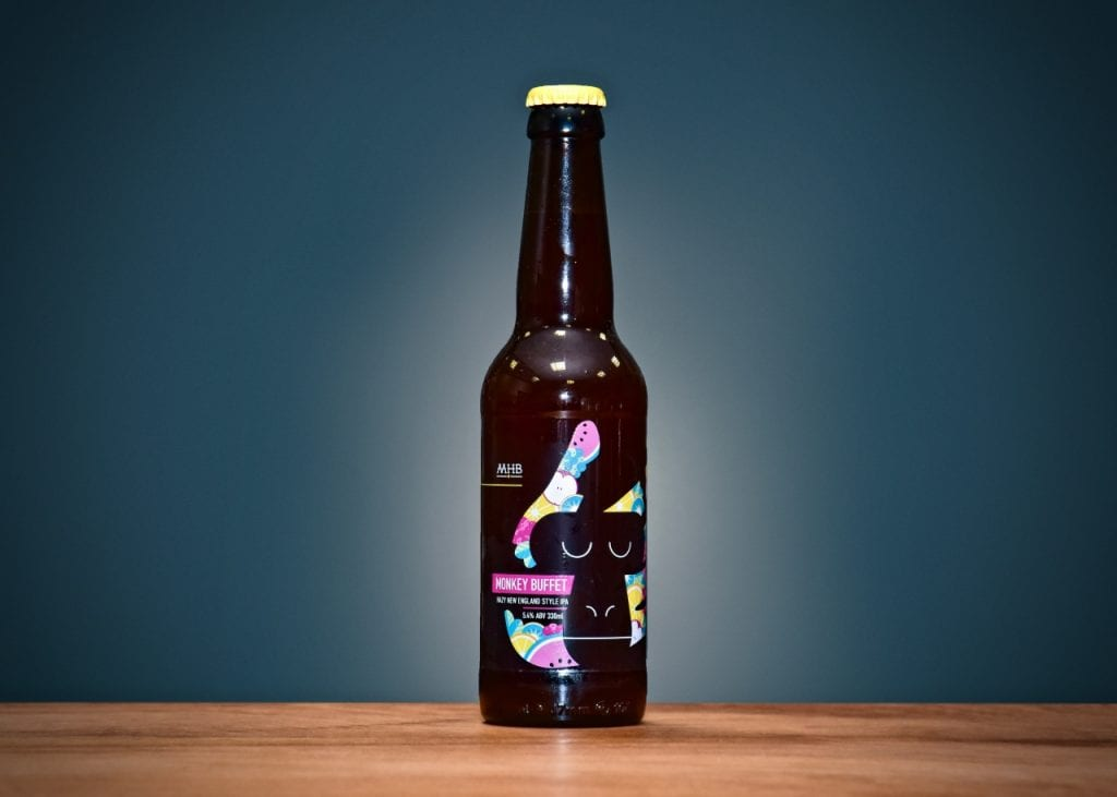 A brown bottle of Many Hands Brew Co. beer against blue background.