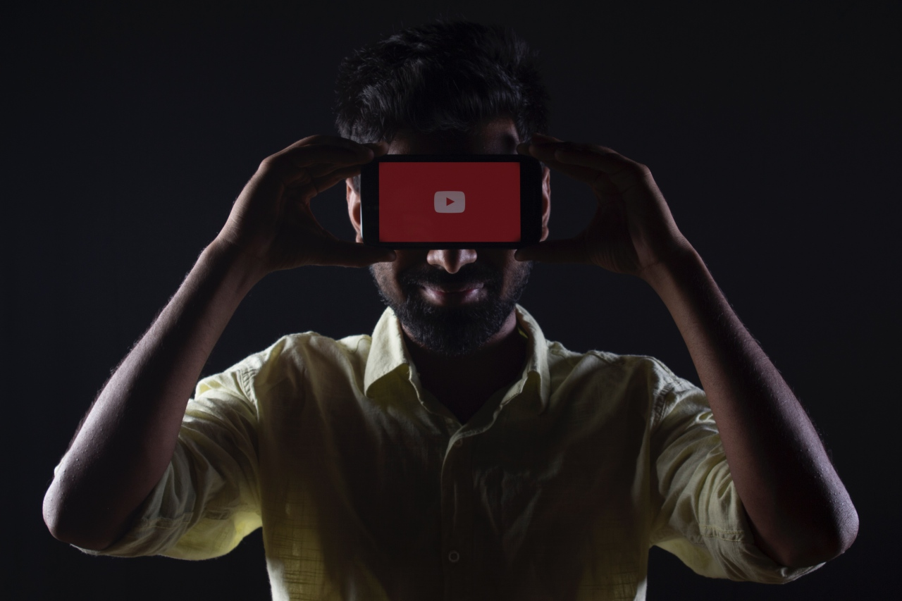 Man holds phone on his head with red Youtube logo on screen online video