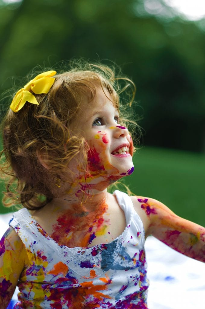 Little girl smiling covered in paint with  yellow bow in her hair.