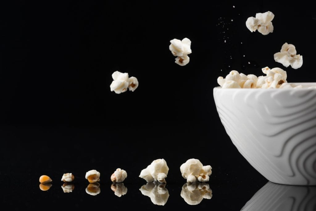 junk foods popcorn from kernel to corn on black surface next to bowl