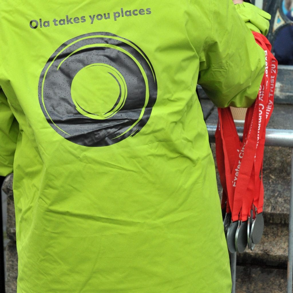 Back of Ola jacket with person holding medals.