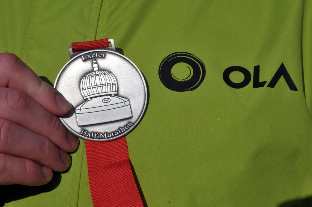 Close up of Exeter half marathon medal and Ola jacket.