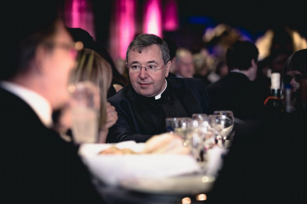 The Very Reverend Jonathan Greener sitting at a table listening to a woman.