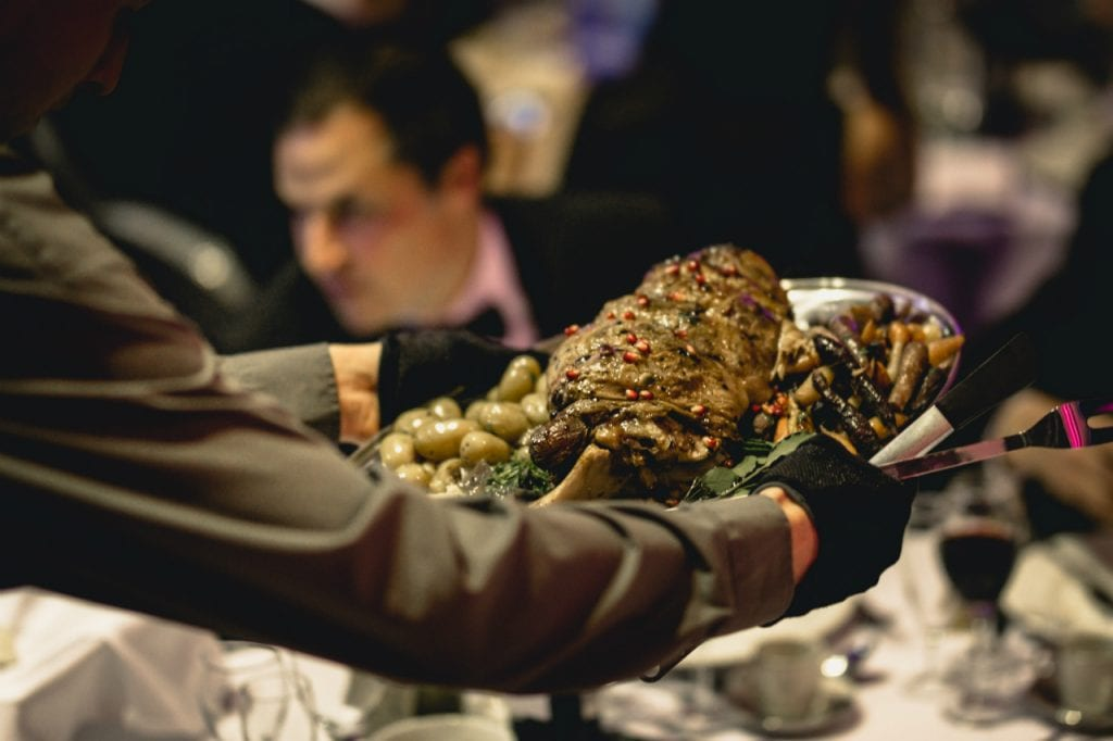Roasted lamb topped with pomegranate seeds and surrounded by vegetables.