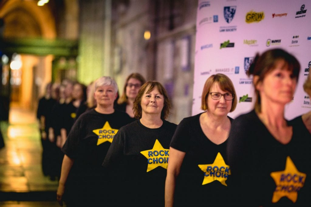 Exeter Rock Choir filing on to the stage wearing black t-shirts with a gold star.