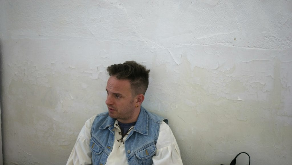 Al Dunn from Le Navet Bete sits leaning against a white wall.
