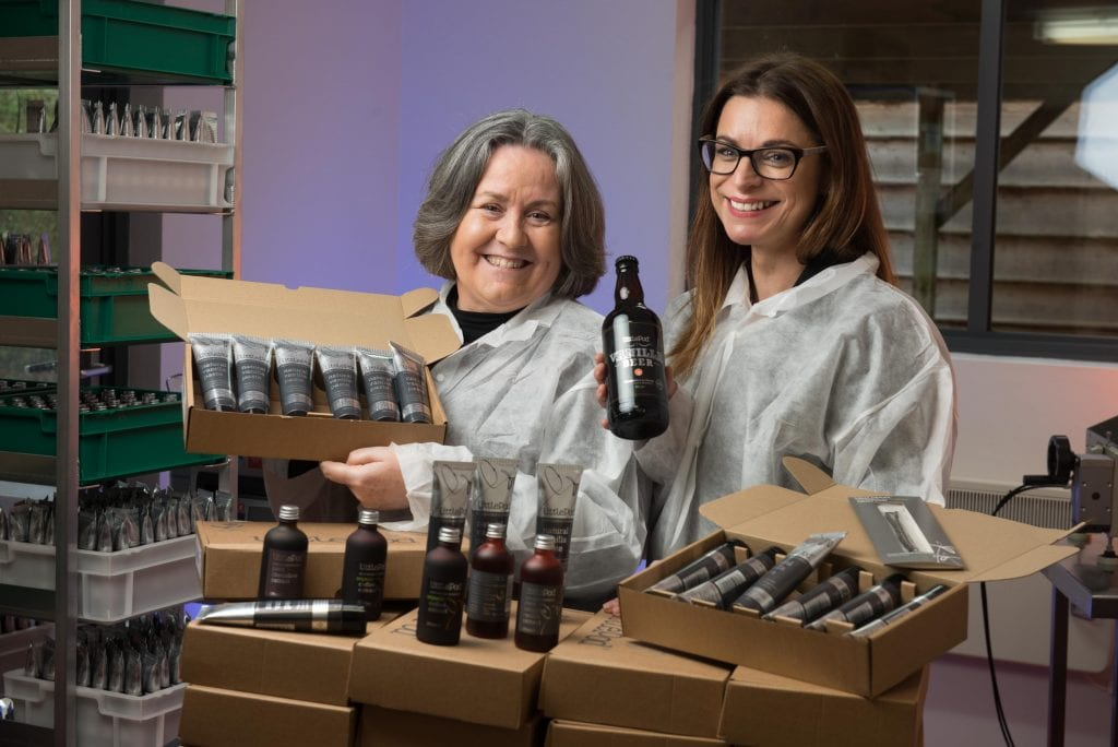 Employees at LittlePod hold up bottles of beer and tubes of vanilla paste.