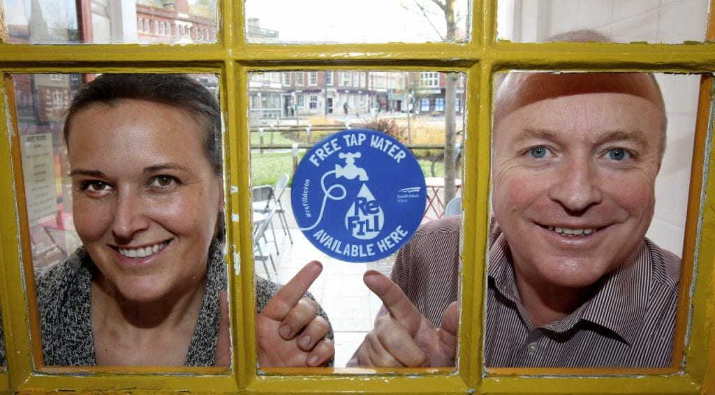 Man and woman point to blue ReFill sign in shop window.
