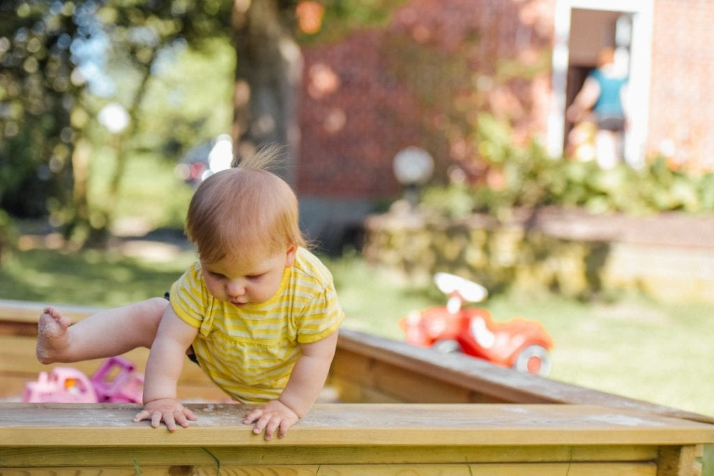 Toddler climbing out of a sandpit.