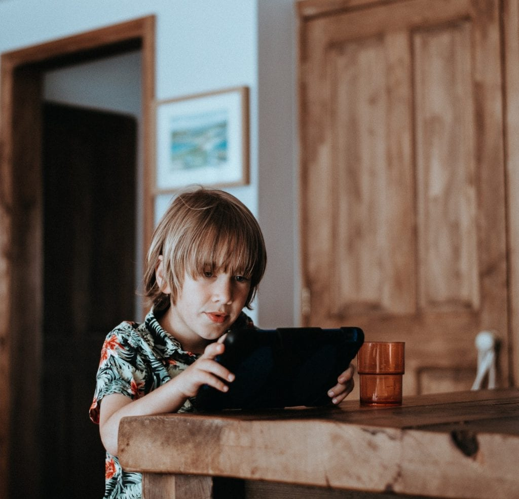 A child holding a tablet at a wooden table sharenting.