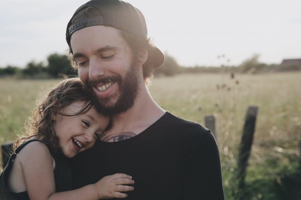 A father and daughter cuddling in a field sharenting.