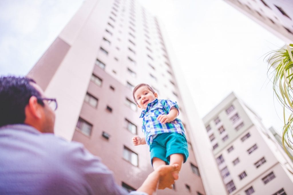 Low angle shot of a man holding a standing toddler in his hand.