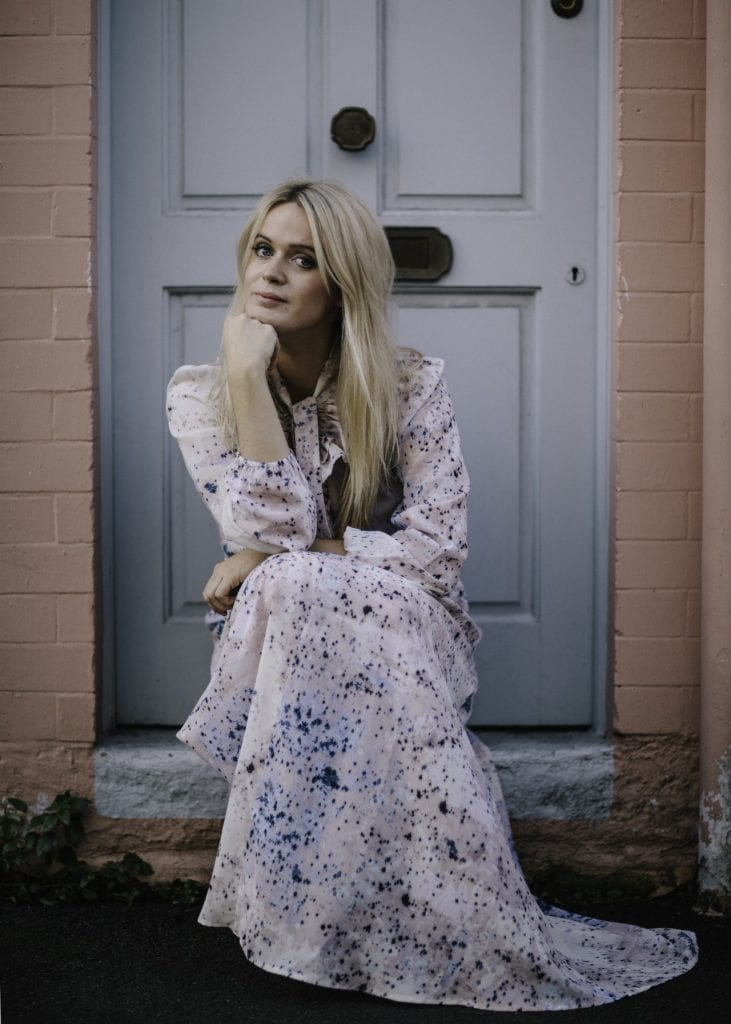 Dolly Alderton sitting on a doorstep wearing a flowing dress.