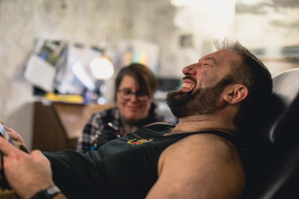 Llew laughing as his arm is tattooed.