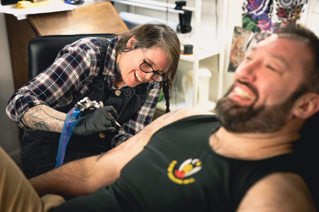 Fleur Tufnell and Llew Nicholls sharing a joke as she tattoos his sleeve