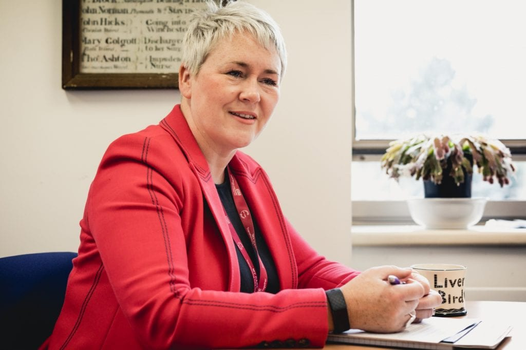 Suzanne Tracey sitting at a desk wearing a red blazer.