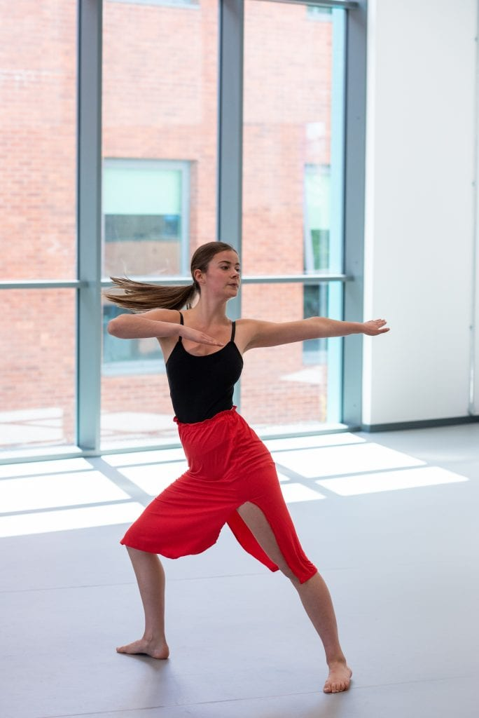 Girl dancing in dance studio wearing black top and red skirt in front of windows