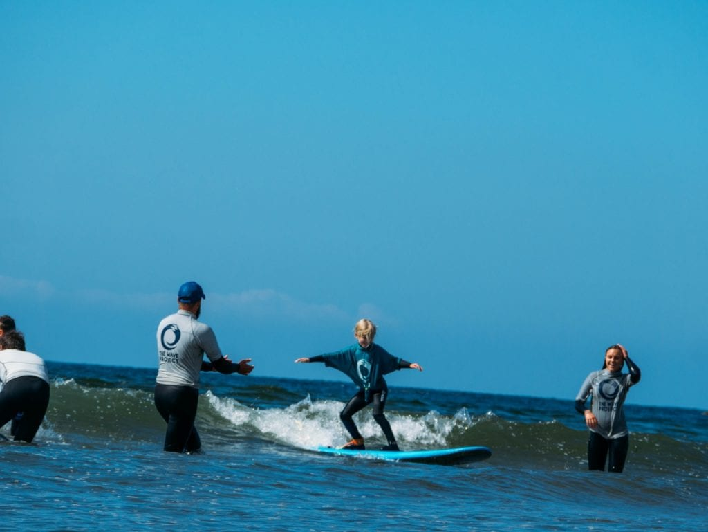 A young girl riding a wave as part of the South Devon Wave Project