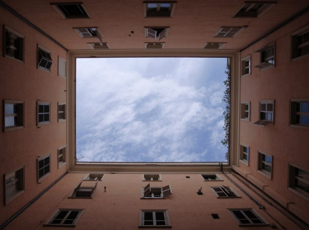 Looking up at a tower block with many windows
