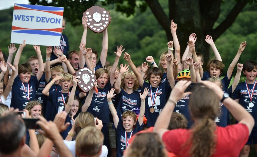 Planet Earth Games children holding medal cheering