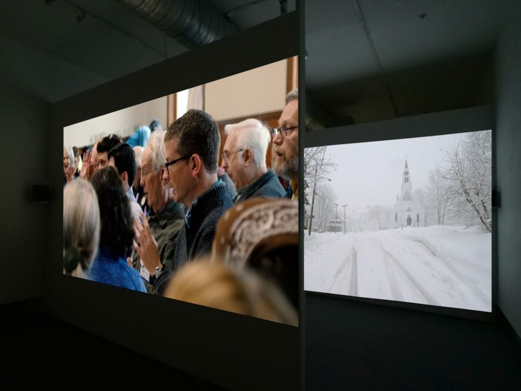 Two of the four screens that form the neighboring|towns installation