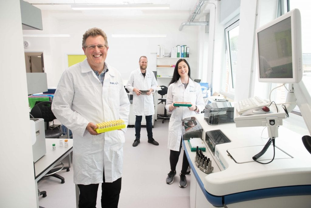 Team man lady lab coat gloves equipment machinery standing smiling