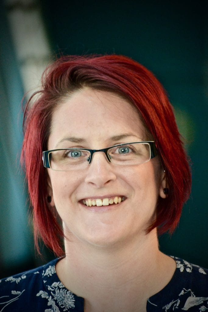 woman red hair glasses smile